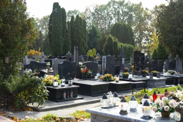 Christian graveyard on a sunny autumn day. All Saints Day. Tombstones decorated with flowers and grave candles.